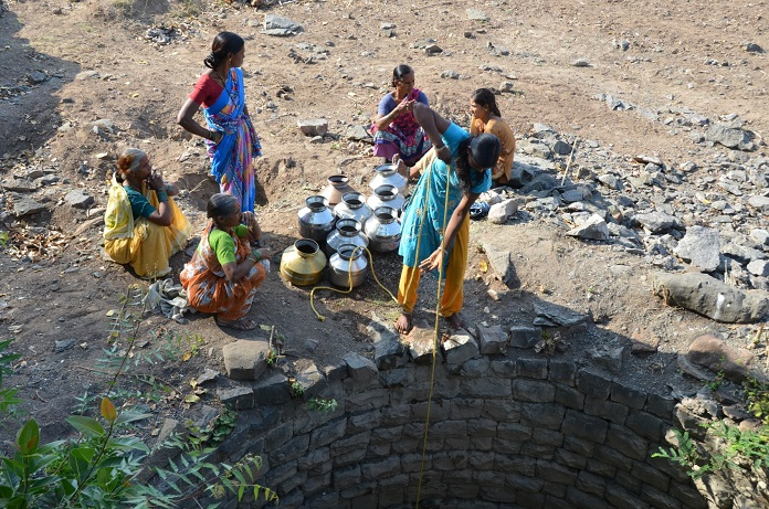 agrarian distress-Women drawing water from a village well. Prior to watershed development and integrated water management, scarcity of water was a way of life for the people of Kumbharwad